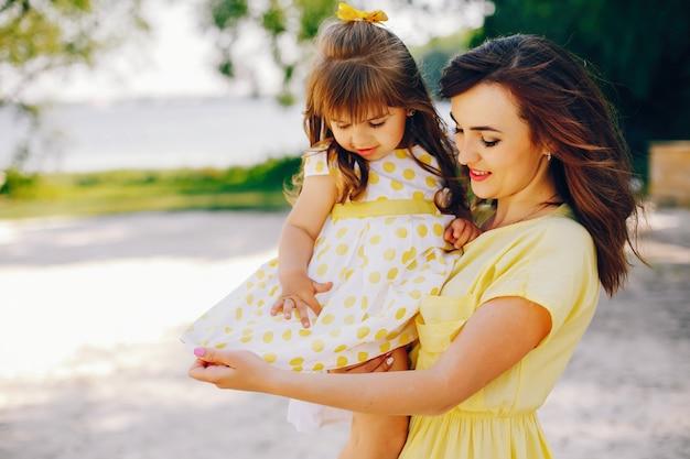 Na słonecznej plaży z żółtym piaskiem, mama chodzi w żółtej sukience i jej mała ładna dziewczyna