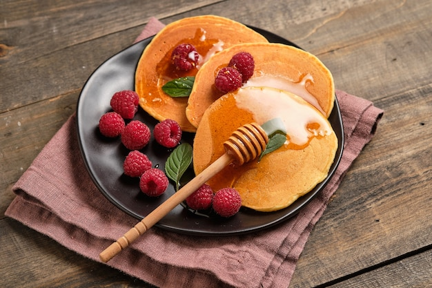 Na śniadanie smakowe naleśniki z miodem i świeżymi malinami świetny deser śniadaniowy