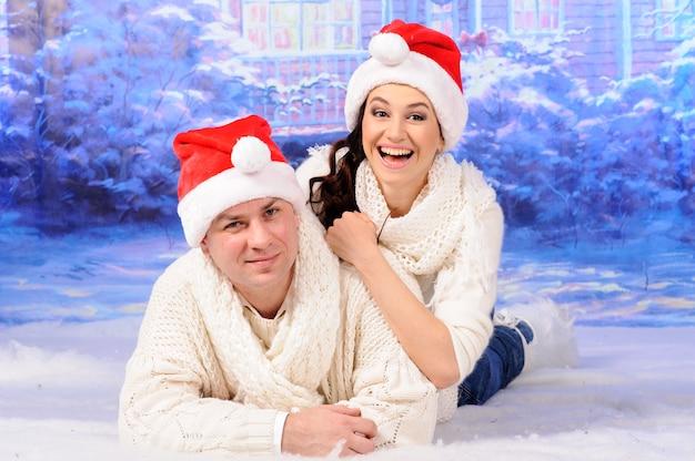 Na śniegu leżą mężczyzna i kobieta w czapkach bożonarodzeniowych.