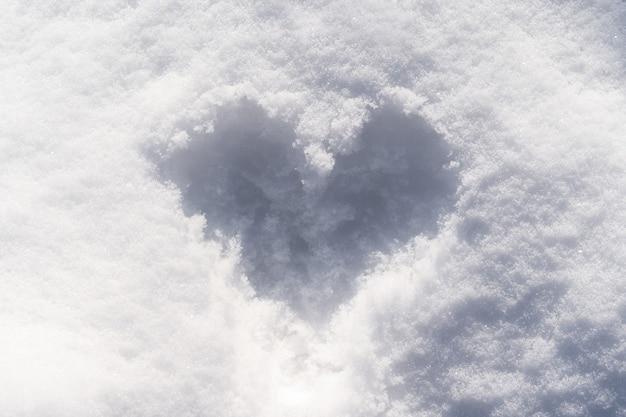 Na śniegu z bliska rysowane jest serce