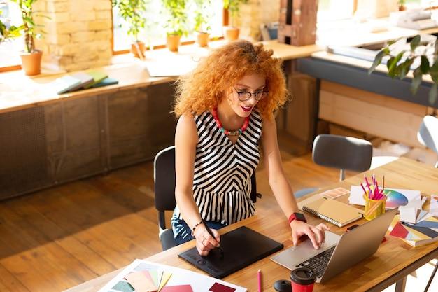 Na sobie bluzkę w paski. rudowłosa kobieta ubrana w pasiastą bluzkę i stylowy naszyjnik ciężko pracuje