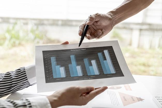 Na spotkaniu dwóch finansistów przedstawia miesięczne zestawienia finansowe, trzymają dokumenty finansowe i wskazują ich w celu wyjaśnienia informacji. koncepcja finansów.