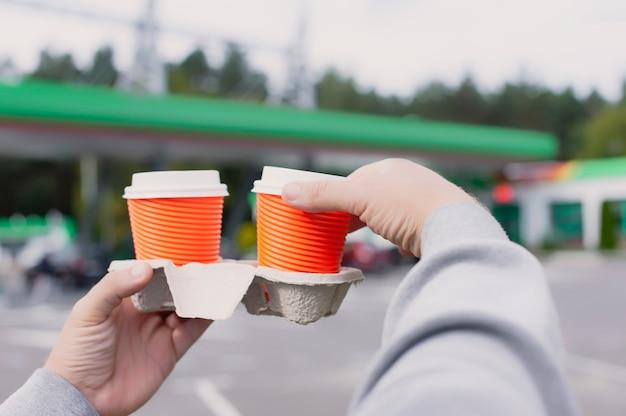 Na stacji benzynowej mężczyzna trzyma w rękach dwie filiżanki kawy