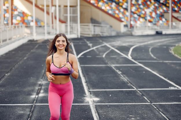 Na stadionie biegnie sportowa dziewczyna w różowym mundurze