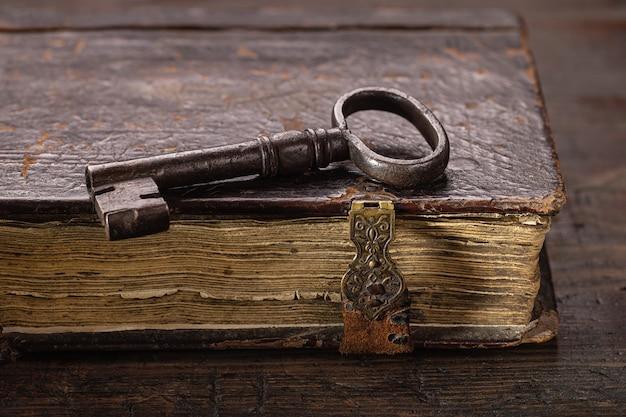 Na starej księdze z zapięciami znajduje się stary klucz wykonany z metalu antyczne przedmioty na ciemnym drewnianym odwrocie