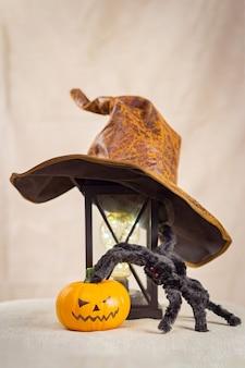 Na starej lampie znajduje się kapelusz wiedźmy, czarny kudłaty pająk z czerwonymi oczami i leżąca obok niego dynia halloween.