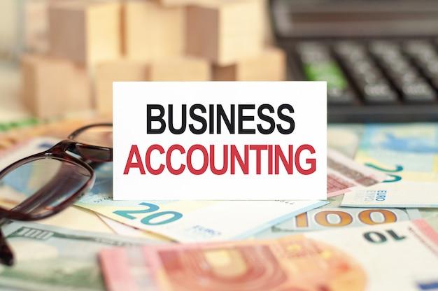 Na stole banknoty, szklanki, kalkulator, drewniane klocki i znak, na którym jest napisany - księgowość biznesowa. koncepcja finansów i ekonomii.