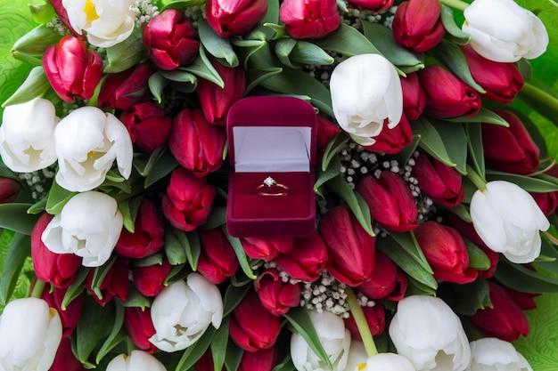 Na stole bukiet czerwonych i białych tulipanów i pudełko ze złotym pierścionkiem z brylantem