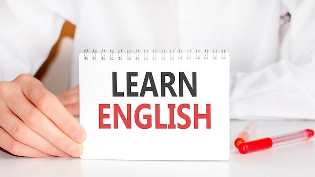 Na stole czerwony marker oraz biała papierowa tabliczka, na której zapisany jest tekst - ucz się angielskiego, czerwonych i czarnych liter. pomysł na biznes.