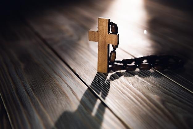 Na stole drewniany krzyż z naszyjnikiem