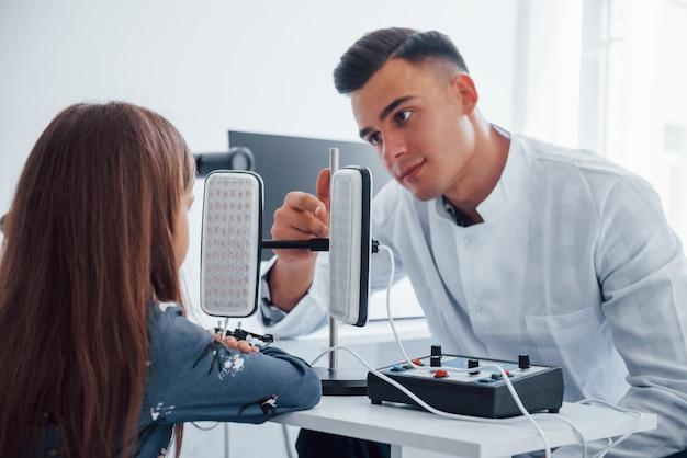 Na stole dwa panele. młody okulista przebywa w klinice z małą kobietą.