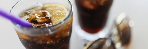 Na stole dwie szklanki z lodem cola i cytryną