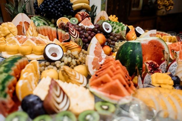 Na stole gastronomicznym znajduje się wiele różnych owoców