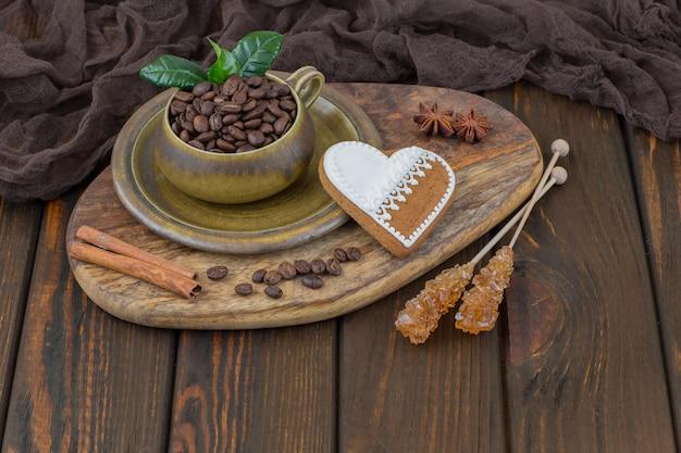 Na stole jest filiżanka z ziaren kawy, cynamonu, piernika w kształcie serca i cukru