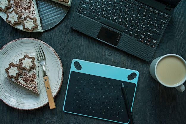 Na stole jest laptop, tablet graficzny i filiżanka kawy.