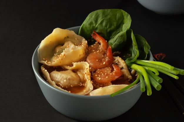 Na stole jest miska zupy z makaronem z krewetkami, wontonami i szpinakiem