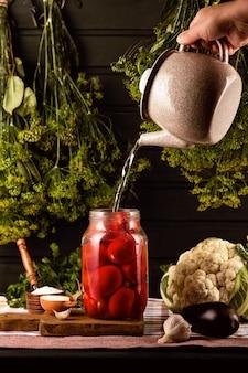 Na stole jest słoik pomidorów, solniczka, czosnek. z czajnika ręka wlewa wrzącą wodę do słoika. nad nimi wiszą kiście koperku.