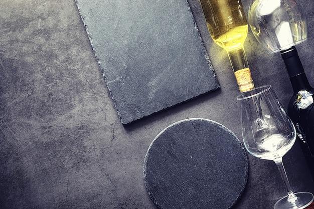 Na stole kieliszek czerwonego wytrawnego wina. ciemna butelka i kieliszek wina.
