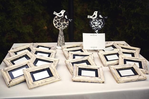 Na stole leżą białe kartki papieru w drewnianych ramkach, a za nimi całująca się dekoracja ptaszków