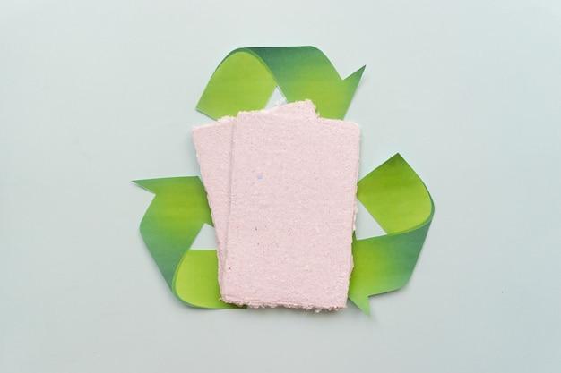 """Na stole leżą kartki papieru i znak """"zero waste"""". koncepcja recyklingu papieru."""