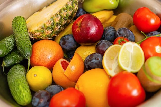 Na stole leżą owoce, warzywa i zielenina, naturalne światło z okna.