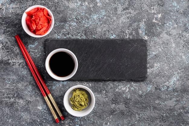 Na stole leżą płasko miodowe imbirowe wasabi i sos sojowy