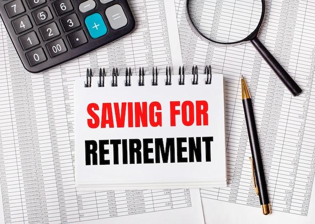 Na stole leżą raporty, lupa, kalkulator, długopis i biały zeszyt z napisem oszczędzamy na emeryturę. pomysł na biznes