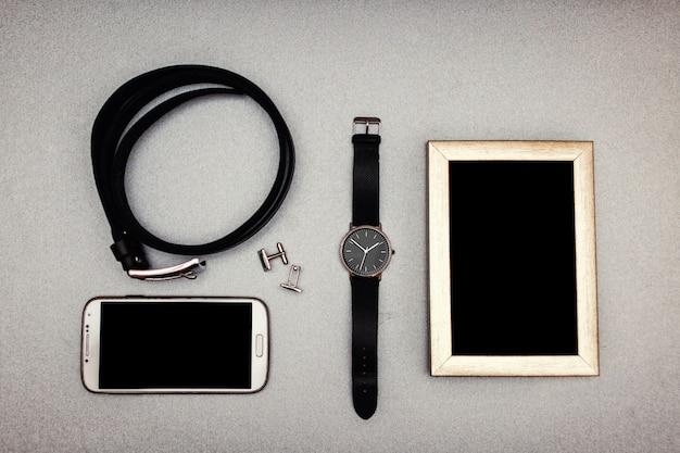 Na stole leżą różne akcesoria związane ze stylem życia, takie jak: telefon, pasek, spinki do mankietów, zegarki