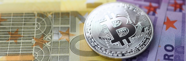 Na stole leżą srebrne bitcoiny z gotówką euro