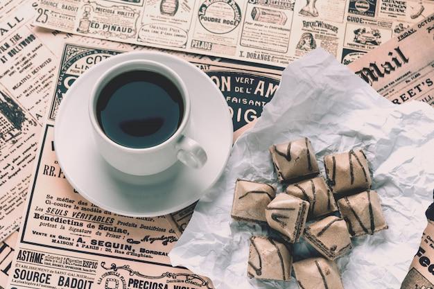 Na stole leżą stare pożółkłe gazety z nowościami i ogłoszeniami
