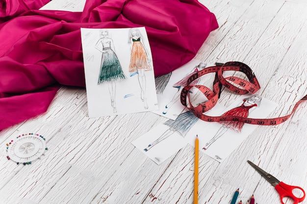 Na stole leżą zdjęcia przedstawiające modele sukienek, różowa tkanina i inne akcesoria do rękodzieła