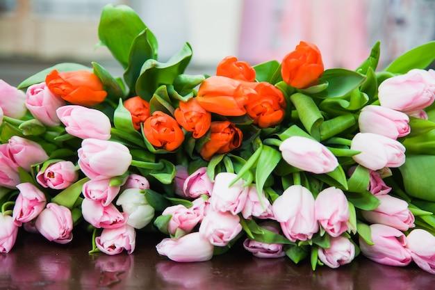 Na stole leżał ogromny, wielokolorowy bukiet tulipanów. jasnym tle wiosennych kwiatów kwiatowych. florystyka i przygotowanie do wakacji. koncepcja kwiatowy wzór