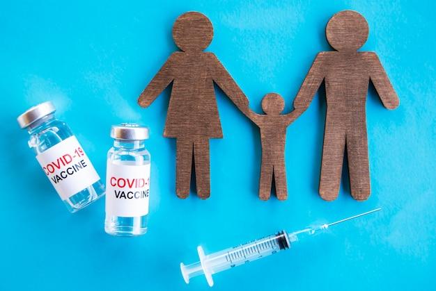 Na stole leżało wycięte rodziny i 19 szczepionek przeciw krowim. pojęcie szczepień rodzinnych. szczepionka koronawirusowa dla dzieci i rodziców