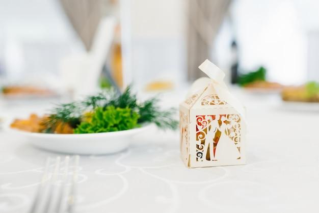 Na stole leży beżowa bonbonniere kartonowa skrzynka na weselu