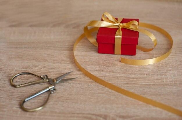 Na stole leży czerwone pudełko ze złotą wstążką i nożyczkami