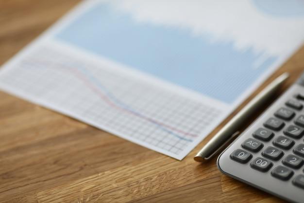 Na stole leży kalkulator i dokument z raportem