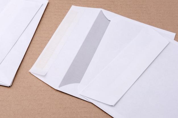 Na stole leży kilka cienkich i białych kopert pocztowych