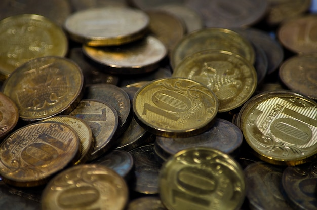 Na stole leży kilka starych i zardzewiałych rosyjskich monet o wartości 10 rubli. tło tekstu. biedny kraj z małymi zarobkami ludności. brak pieniędzy. skopiuj miejsce
