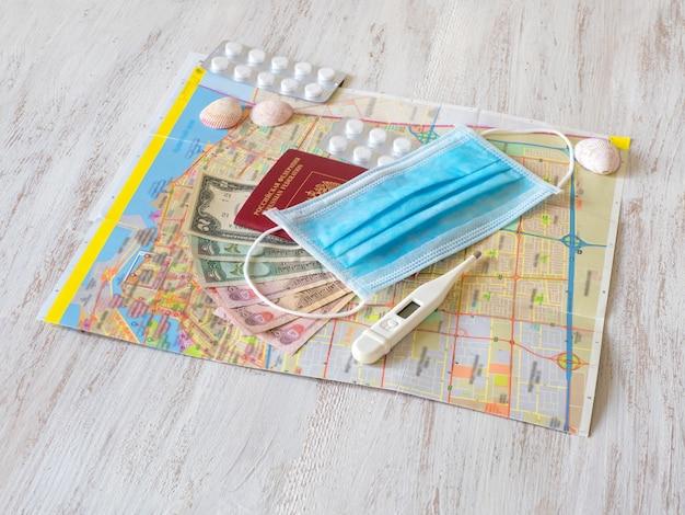 Na stole leży maska medyczna, mapa, pigułki, paszport i pieniądze. koncepcja podróży