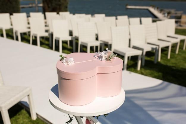 Na stole leży różowe pudełko na prezenty w kształcie serca