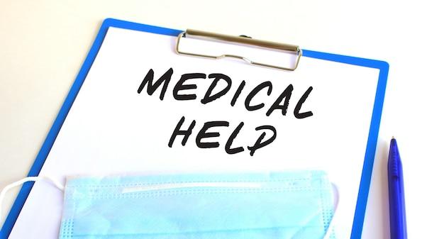 Na stole leży schowek z medyczną maską ochronną. napis pomoc medyczna.