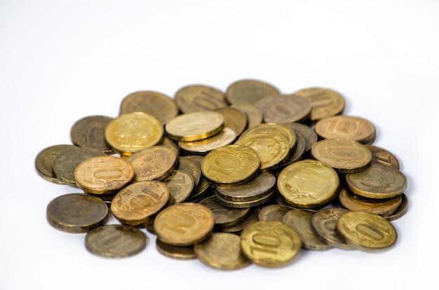 Na stole leży stos starych i zardzewiałych rosyjskich monet o wartości 10 rubli, na białym tle. biedny kraj z niewielkimi wynagrodzeniami ludności. mało pieniędzy. skopiuj miejsce