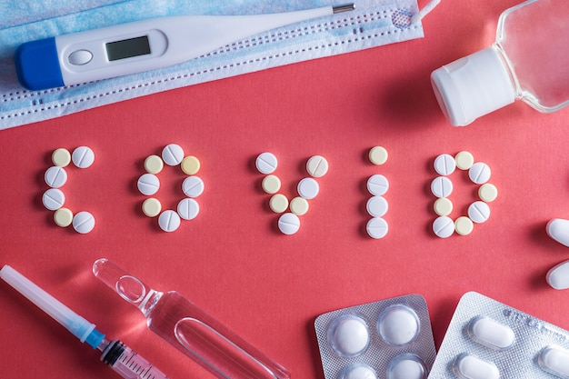Na stole napis covid -19 stetoskopowa maska ochronna na tabletki. infekcja koronawirusem i koncepcja kontroli pandemii