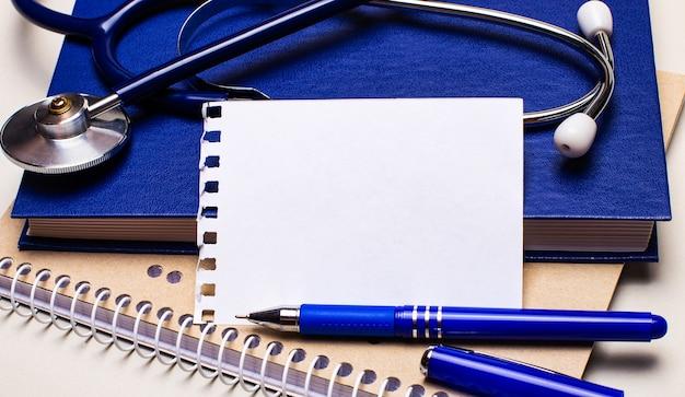 Na stole notesy, stetoskop, długopis i kartka z miejscem na wpisanie tekstu. koncepcja medyczna