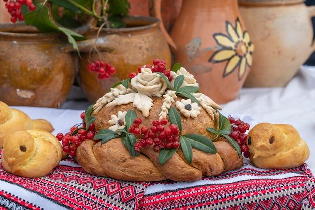 Na stole, obok haftowanego ręcznika, leży świeży ukraiński dekorowany świeży bochenek z solą. ukraińskie i rosyjskie tradycje weselne. smaczne ciasto, z bliska