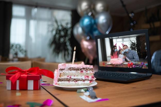 Na stole obok laptopa stoi duży kawałek ciasta i świeca. rodzina świętuje w internecie