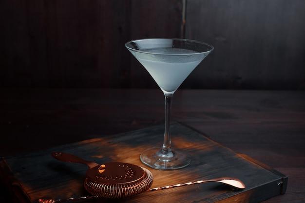 """Na stole obok łyżeczki i sitka pyszny koktajl alkoholowy """"margarita"""" na bazie tequili w eleganckim kieliszku. profesjonalne narzędzia do produkcji napojów alkoholowych. zbliżenie."""