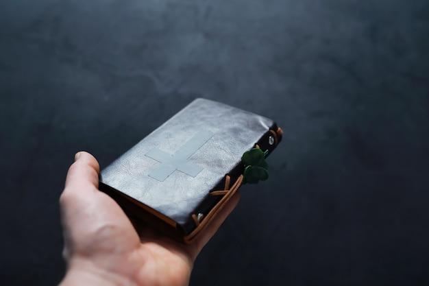 Na stole oprawiona w skórę biblia. religijne chrześcijańskie święto irlandzkie. czterolistna koniczyna symbol szczęścia.