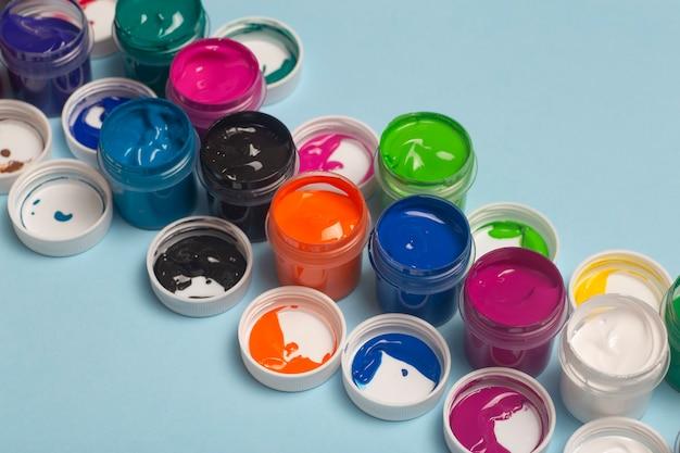 Na stole otwarte są farby akrylowe w różnych kolorach do rysowania. jasne kolorowe tło z puszek po farbie