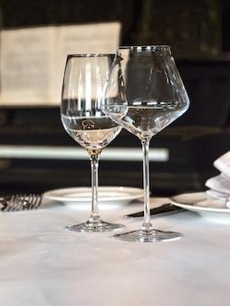 Na stole podawane są puste kieliszki do wina, orientacja pionowa.